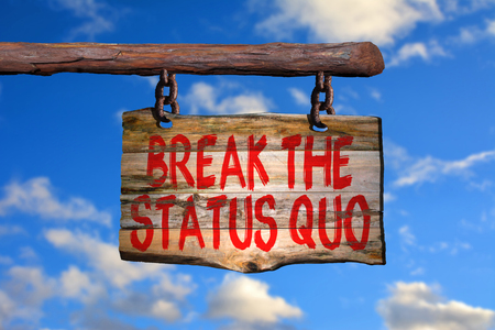 quo: Break the status quo motivational phrase sign on old wood with blurred background