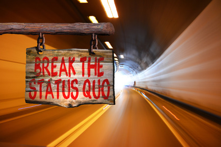 Break the status quo motivational phrase sign on old wood with blurred background