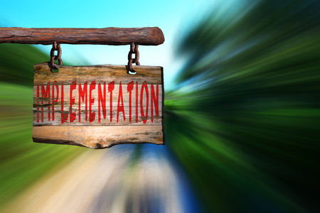 implementation: Implementation motivational phrase sign on old wood with blurred background Stock Photo