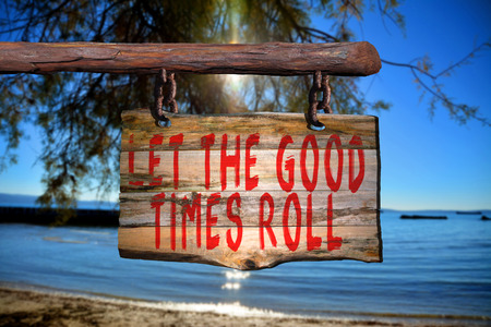 good times: Let the good times roll motivational phrase sign on old wood with blurred background