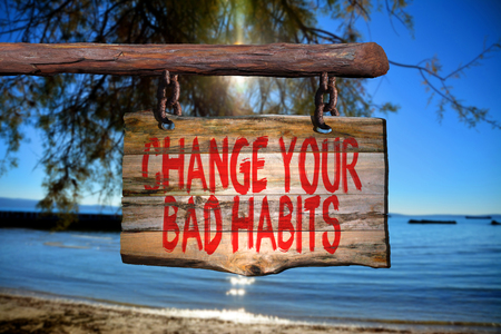 bad habits: Change your bad habits motivational phrase sign on old wood with blurred background Stock Photo