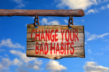 malos habitos: Cambiar los malos hábitos signo frase de motivación en la madera vieja con el fondo borroso