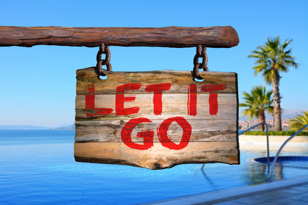 Let it go motivational phrase sign on old wood with blurred background
