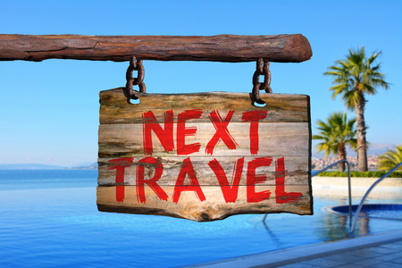 Next travel motivational phrase sign on old wood with blurred background