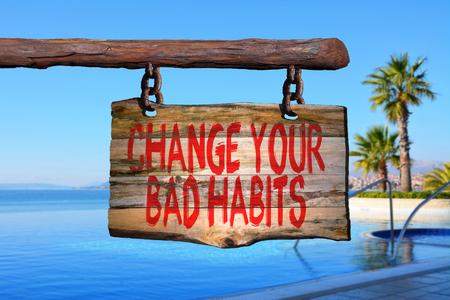 bad habits: Cambiar los malos hábitos signo frase de motivación en la madera vieja con el fondo borroso