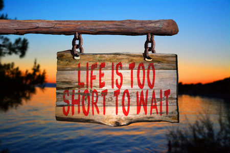 wait sign: Life is too short to wait motivational phrase sign on old wood with blurred background Stock Photo