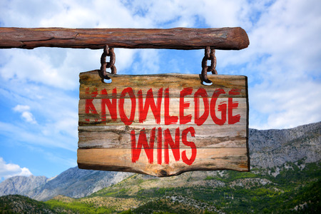 wins: Knowledge wins motivational phrase sign on old wood with blurred background