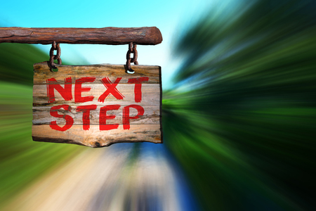 Next step motivational phrase sign on old wood with blurred background Stock Photo