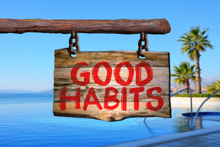 good habits: Good habits motivational phrase sign on old wood with blurred background