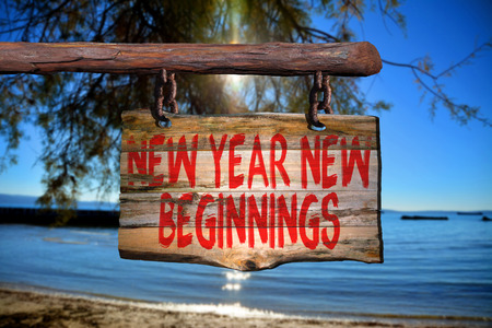 new beginnings: New year new beginnings motivational phrase sign on old wood with blurred background