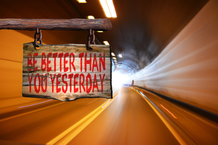than: Be better than you yesterday motivational phrase sign on old wood with blurred background