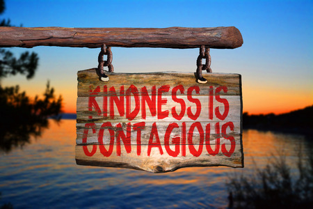 contagious: Kindness is contagious motivational phrase sign on old wood with blurred background