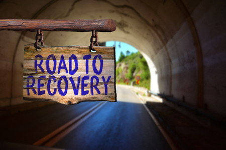 road to recovery: Road to recovery motivational phrase sign on old wood with blurred background Stock Photo