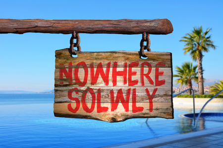 enjoy life: Nowhere solwly motivational phrase sign on old wood with blurred background