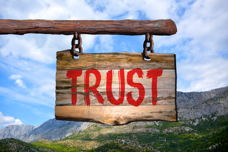 phrase: Trust motivational phrase sign on old wood with blurred background