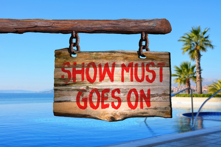 show must goes on motivational phrase sign on old wood with blurred background Stock Photo