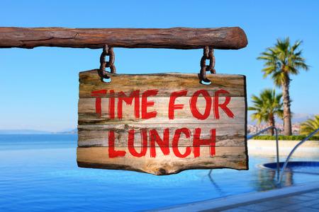 Zeit für das Mittagessen Motivphrase Zeichen auf altem Holz mit unscharfen Hintergrund