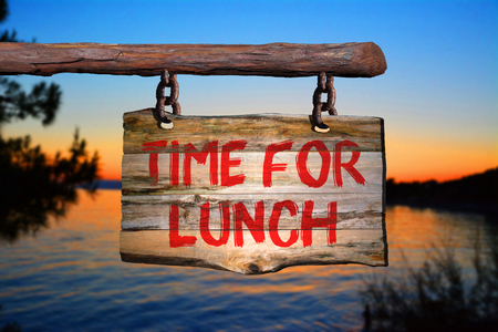 Time for lunch motivational phrase sign on old wood with blurred background
