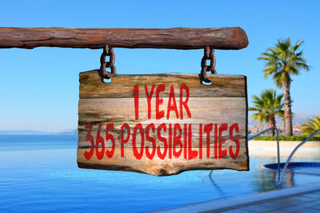 1 year 365 possibilities motivational phrase sign on old wood with blurred background