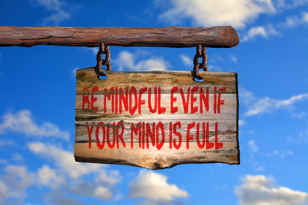 mindful: Be mindful even if your mind is full motivational phrase sign on old wood with blurred background