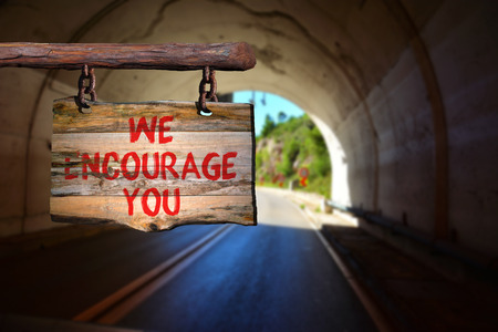 encourage: We encourage you motivational phrase sign on old wood with blurred background Stock Photo