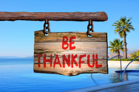 Be thankful motivational phrase sign on old wood with blurred background