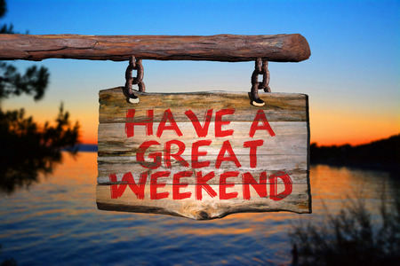 Have a great weekend motivational phrase sign on old wood with blurred background