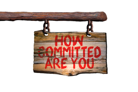 committed: How committed are you motivational phrase sign on old wood with blurred background