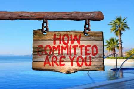 How committed are you motivational phrase sign on old wood with blurred background