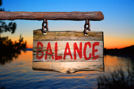 Balance motivational phrase sign on old wood with blurred background