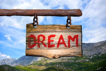 Dream motivational phrase sign on old wood with blurred background