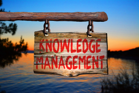 Knowledge management motivational phrase sign on old wood with blurred background
