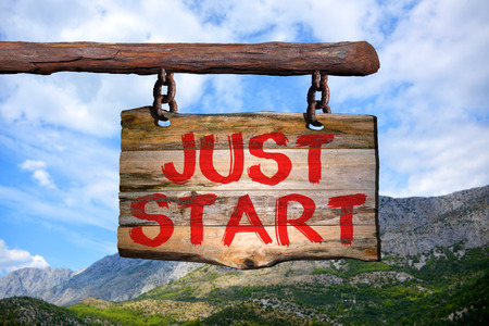 optimismo: just start motivational phrase sign on old wood with blurred background Foto de archivo