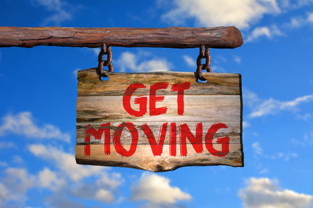 Get moving motivational phrase sign on old wood with blurred background