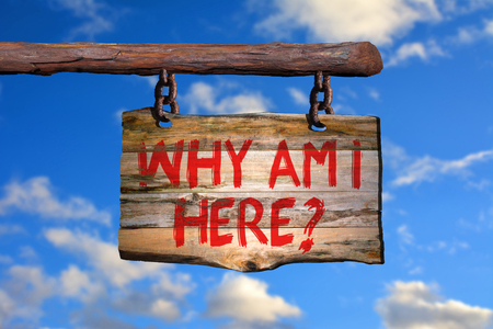 Why am i here? motivational phrase sign on old wood with blurred background