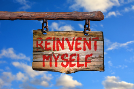 believe: reinvent myself motivational phrase sign on old wood with blurred background