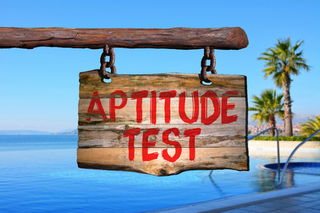 Aptitude test motivational phrase sign on old wood with blurred background