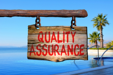Quality assurance motivational phrase sign on old wood with blurred background