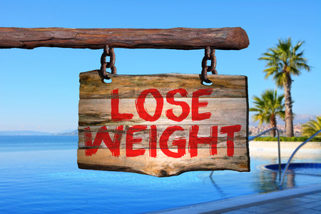 Lose weight motivational phrase sign on old wood with blurred background Stock Photo