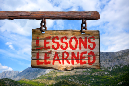 learned: Lessons learned motivational phrase sign on old wood with blurred background Stock Photo
