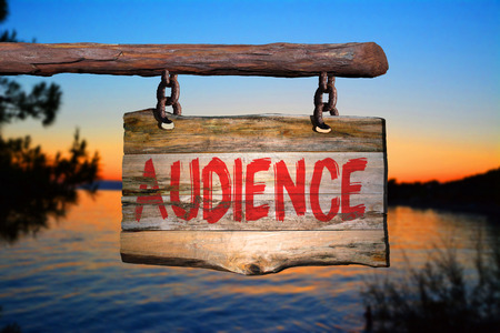 Audience motivational phrase sign on old wood with blurred background