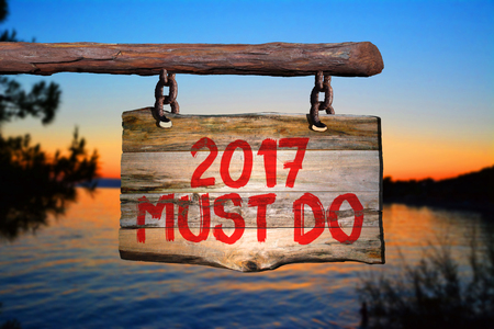2017 must do motivational phrase sign on old wood with blurred background