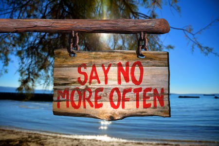 Say no more often motivational phrase sign on old wood with blurred background Stock Photo