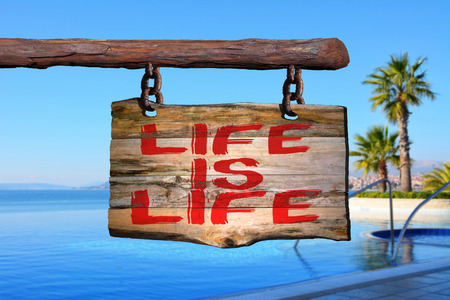 Life is life motivational phrase sign on old wood with blurred background Stock Photo
