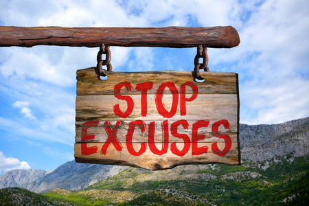 Stop excuses motivational phrase sign on old wood with blurred background