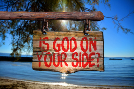 Is god on your side? motivational phrase sign on old wood with blurred background