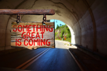 Something great is coming motivational phrase sign on old wood with blurred background