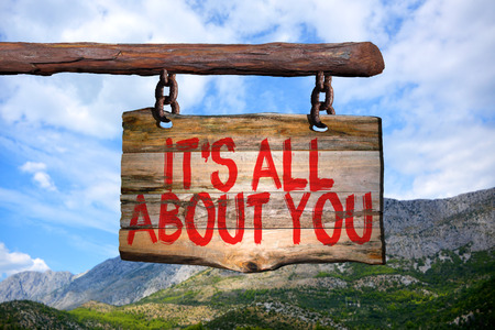 Its all about you motivational phrase sign on old wood with blurred background