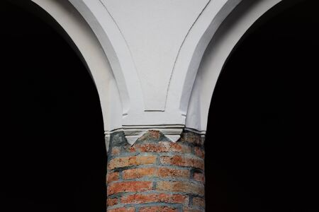 Detail of a historic brick pillar with plastered transition to the top, dividing against a dark background in the center of the painting Reklamní fotografie