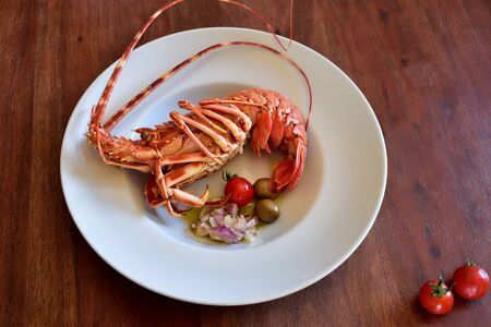 A boiled lobster lies in a white plate with side dishes on a rustic wooden table as a background